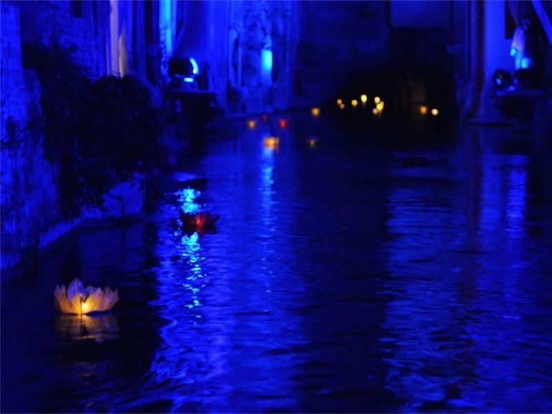 Le lanterne galleggianti luminosi di carta di riso in colori e misure diverse sul fiume canale